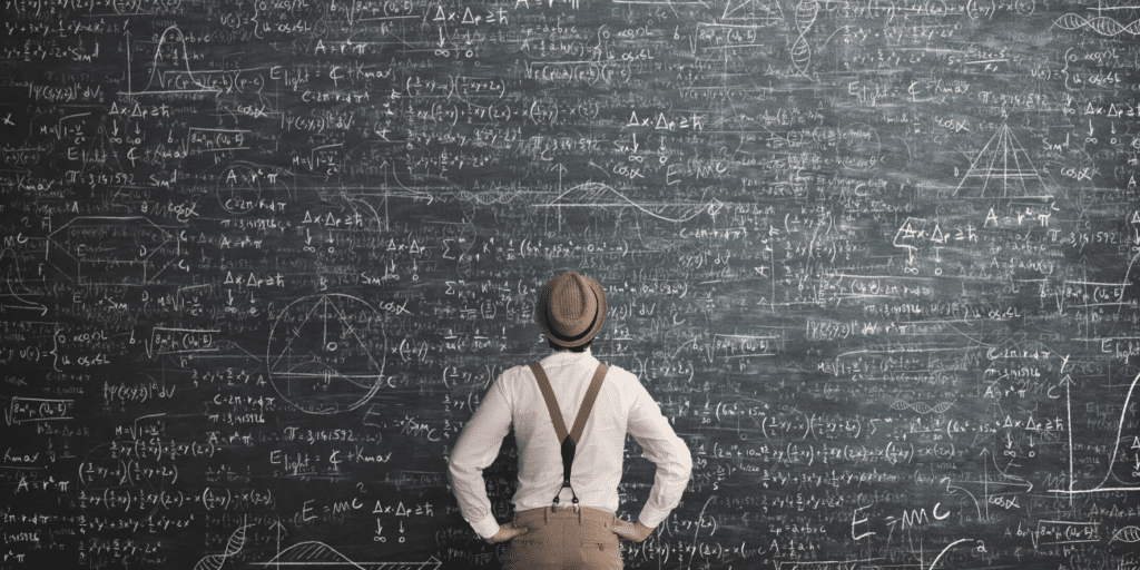 man standing in front of black board trying to solve a problem