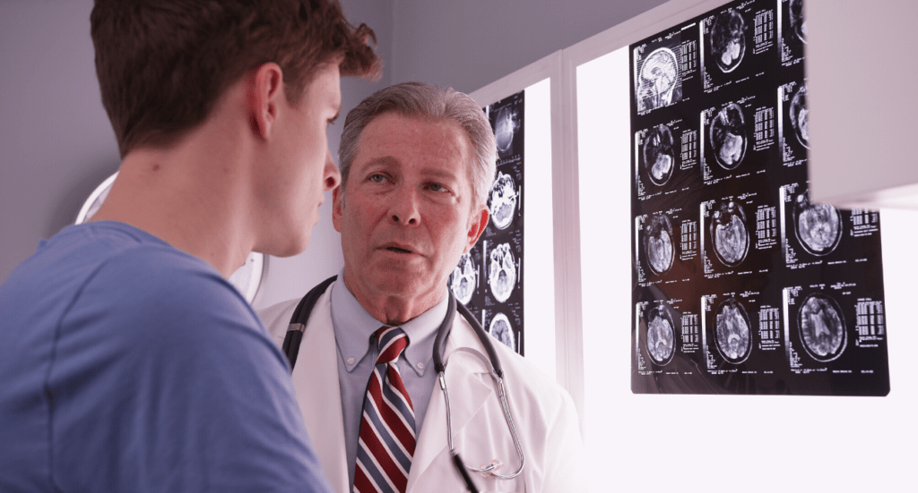 young man with doctor, looking at brain scans