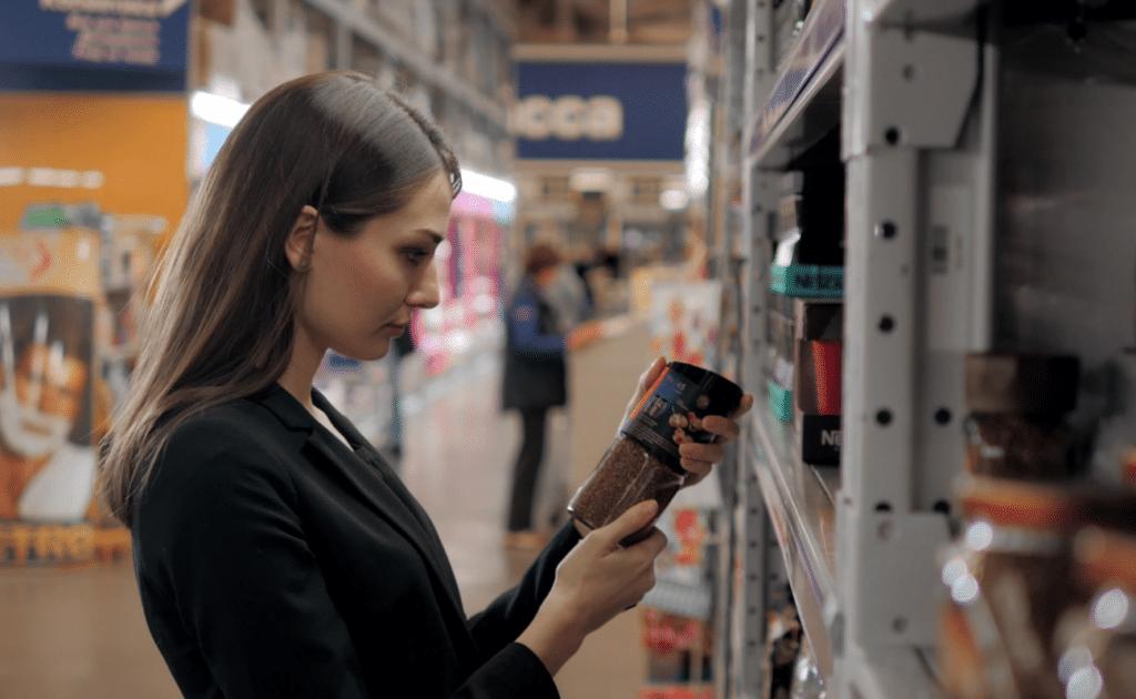 women choosing coffee in store aisle